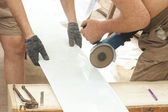 Construction activity: two workers sawing plastic panel — Stock fotografie