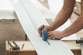 Construction activity: worker drawing line on plastic panel — Stok fotoğraf