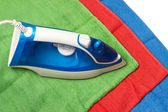 Flat smoothing iron on coloured bath towels — Stock Photo
