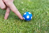 Man hand playing role of soccer player with small blue ball — 图库照片