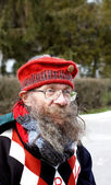 Homeless senior in funny red cap — Stock Photo