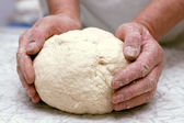 Hands of woman baker kneading dough — Stock Photo