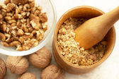 Walnuts: full, cracked and grinded. Focus on masher. — Stock Photo