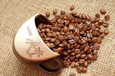 Coffe beans strewed from cup into sacking — Stock Photo