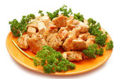 Pieaces of fried checken and parsley on orange plate — Stock Photo