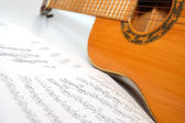 Spanish guitar and paper leaves with notes — Stock Photo