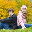 Brother with sister sit against yellow leaves — Stock Photo