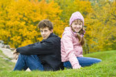 Brother with sister sit against yellow leaves — Fotografia Stock