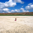 Girl is sitting on a salt lake — Stock Photo