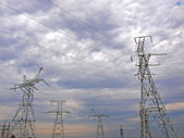 Masts of electric mains and cloudy sky — Stock Photo