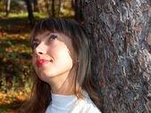 Leende ung kvinna och en tall — Stockfoto