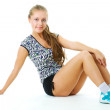 Stock Photo: Young woman in sports wear sitting on floor