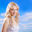 Royalty-Free Stock Photo: Pretty woman smiling against blue sky