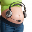 Pregnant belly with headphones — Stock Photo