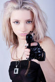 Glamorous young sexy girl on grey with gun — Stock Photo