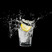 Splash in a glass with lemon and ice on a black background — Stock Photo