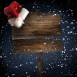 Wooden sign with santa hat on snowy background — Stock Photo