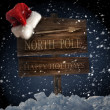 Wooden sign with santa hat on snowy background — Zdjęcie stockowe #4175471