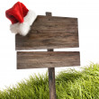 Weathered wooden sign with santa hat on white — 图库照片