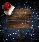 Placa de madeira com chapéu de papai noel em fundo nevado — Foto Stock