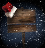 Wooden sign with santa hat on snowy background — Photo