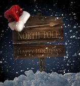 Wooden sign with santa hat on snowy background — ストック写真
