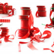Different sizes of red ribbons and gift wrapped boxes on white - Stok fotoğraf