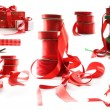 Different sizes of red ribbons and gift wrapped boxes on white - Stock Photo