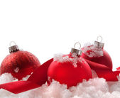 Red Christmas balls and ribbon in snow on white — Stock Photo