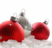 Three red Christmas balls in the snow — Zdjęcie stockowe