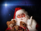 Santa smiling holding toy teddy bears — Stock Photo