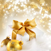 Gold ribbon gift with holiday background — Stock Photo