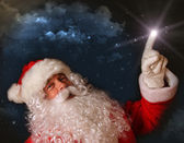 Santa pointing with magical light to the sky — Stock Photo