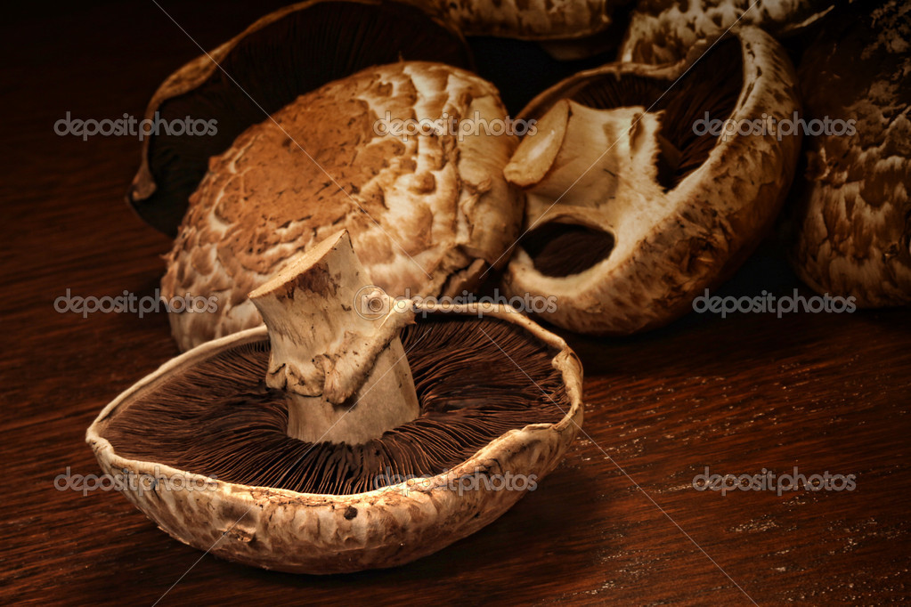 Fresh portobello mushrooms on wooden surface  — Stock Photo #4340510