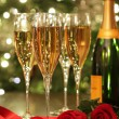 Glasses of Champagne with red roses - Stock Photo