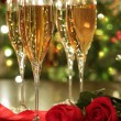 Glasses of champagne and red roses — Stock Photo