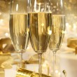 Glasses of champagne and gifts for new years - Stock Photo