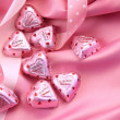 Valentine's chocolate hearts on pink satin — Stok fotoğraf