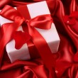 Red ribbon holiday gift on satin — Stock Photo #4439024