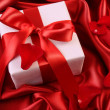Red ribbon holiday gift on satin — Stock Photo