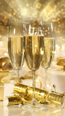 Glasses of champagne and gifts for new years — Stock Photo