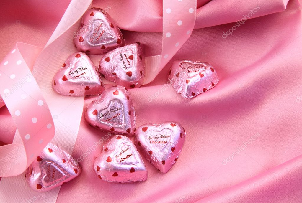 Valentine's chocolate hearts on pink satin with ribbon — Stok fotoğraf #4439016