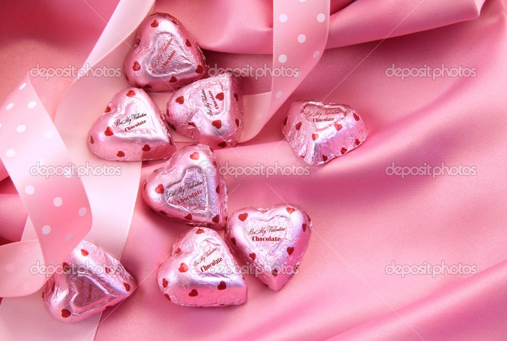 Valentine's chocolate hearts on pink satin with ribbon — Stockfoto #4439016