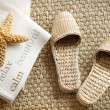 Spa slippers on seagrass carpet with towels - Stock Photo