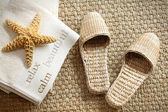 Spa slippers on seagrass carpet with towels — Stock Photo