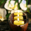 Spa setting with pebbles, candles and flowers - Stock Photo