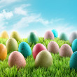 Colorful Easter eggs in a field of grass - Stock Photo