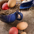 Easter eggs in blue enamel cup with straw - Stock Photo