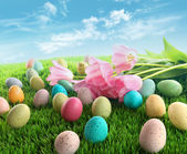 Easter eggs with pink tulips on grass — Stock Photo