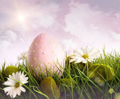 Large pink easter with flowers in tall grass — Stock Photo